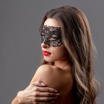 Schöne junge frau mit maske