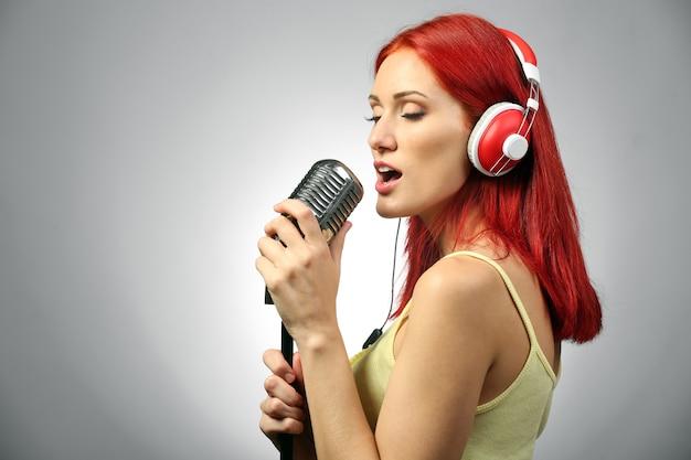 Schöne junge frau mit mikrofon und kopfhörern auf grau
