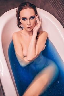 Schöne junge frau mit mode-make-up, die das baden in einer retro-wanne voll des farbigen blauen kosmischen badebombenwassers aufwirft. spa- und schönheitssalonkonzept, körper- und hautpflege.