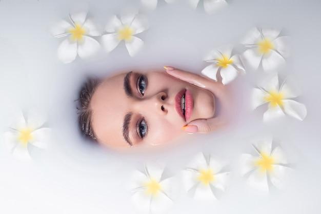 Schöne junge frau mit natürlichem make-up und weißen blumen, die im milchbad entspannen.