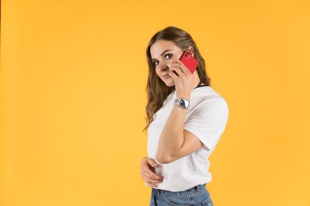 Schöne junge frau mit neuem modell iphone und apfeluhr, die auf smartphone spricht.