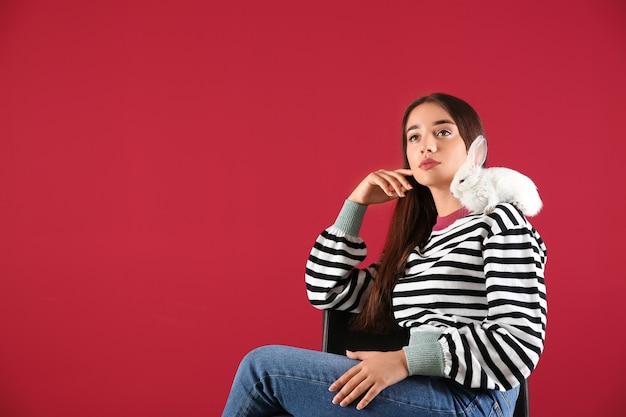 Schöne junge frau mit niedlichem hasen, der auf stuhl sitzt