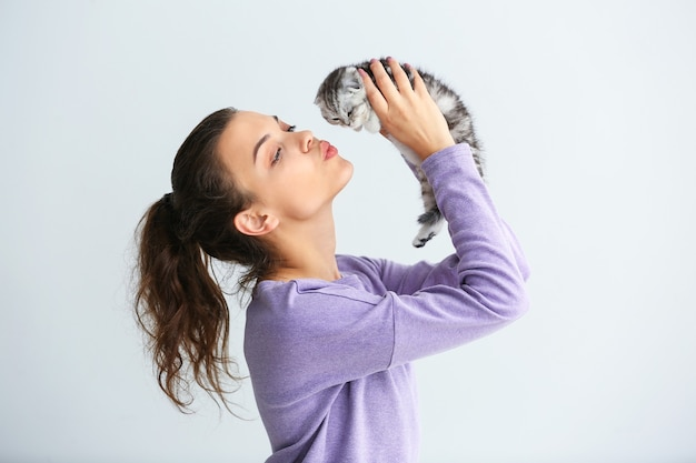 Schöne junge frau mit niedlichem kleinen kätzchen auf heller oberfläche