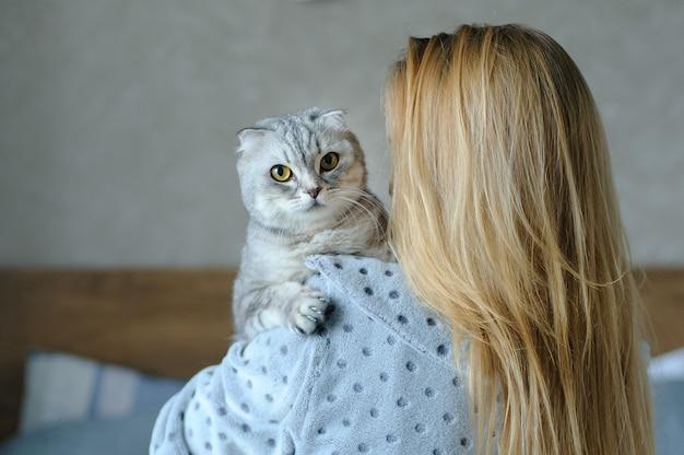Schöne junge frau mit niedlicher katze auf einem bett