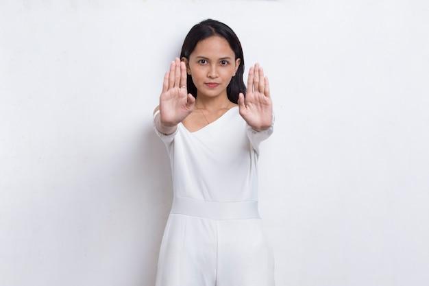 Schöne junge frau mit offener hand, die stoppschild mit ernster ausdrucksverteidigungsgeste tut