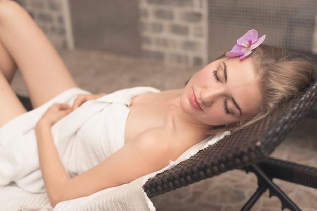 Schöne junge frau mit orchideenblume auf ihrem kopf, der auf klappstuhl am badekurort schläft