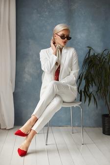 Schöne junge frau mit perfektem blondem haar im eleganten weißen anzug und in den roten schuhen, die im studio aufwerfen.