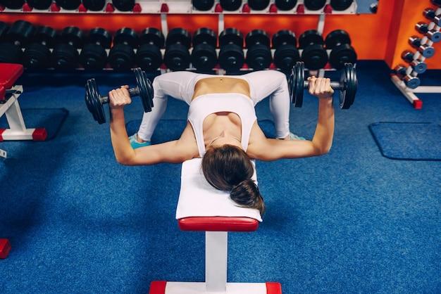 Schöne junge frau mit perfektem körper, der übungen für die brust im fitnessstudio tut