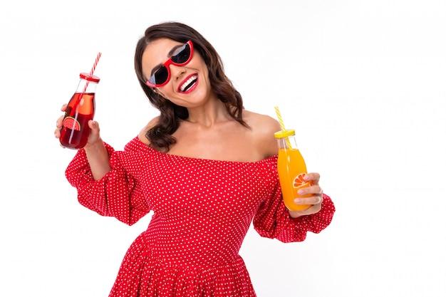 Schöne junge frau mit perfektem lächeln, sonnenbrille trinkt den erdbeersaft und lächelt, lokalisiert