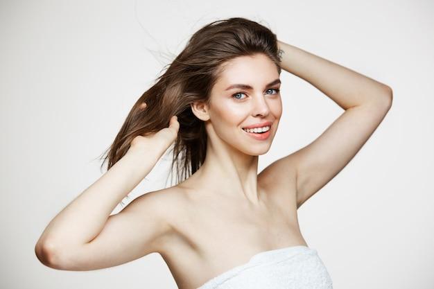 Schöne junge frau mit perfekter sauberer haut lächelnd, die haare über weißer wand berührt. gesichtsbehandlung.