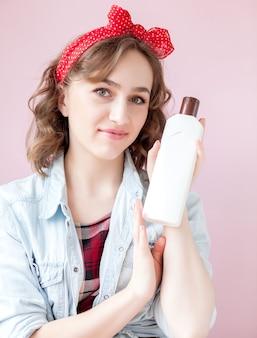 Schöne junge frau mit pin-up-make-up und frisur mit reinigungswerkzeugen auf rosa.