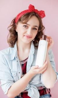 Schöne junge frau mit pin-up-make-up und frisur mit reinigungswerkzeugen