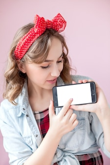 Schöne junge frau mit pin-up-make-up und frisur über rosa mit handy mit kopierraum.