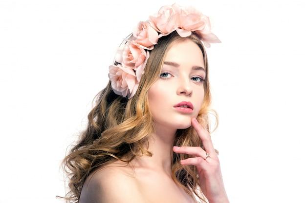 Schöne junge frau mit rosa blumen auf dem kopf