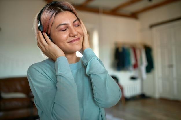 Schöne junge frau mit rosa haaren und nasenpiercing, die augen geschlossen hält und musik hört