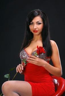 Schöne junge frau mit rose auf dunklem hintergrund