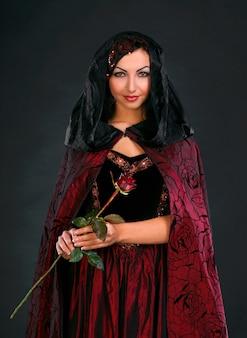 Schöne junge frau mit rose in mittelalterlicher tracht auf dunklem hintergrund