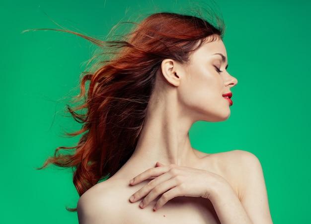 Schöne junge frau mit rotem haar nackte schultern lippen helles make-up