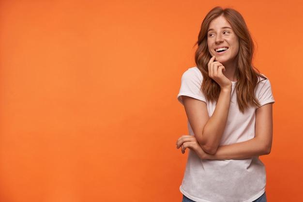 Schöne junge frau mit roten haaren hält ihr kinn mit der hand, schaut zur seite und lächelt fröhlich, trägt lässiges t-shirt