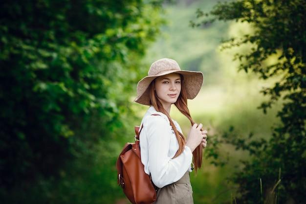 Schöne junge frau mit roten haaren, in einem hut und mit einem rucksack am rande des waldes. schönes rothaariges mädchen auf einem spaziergang