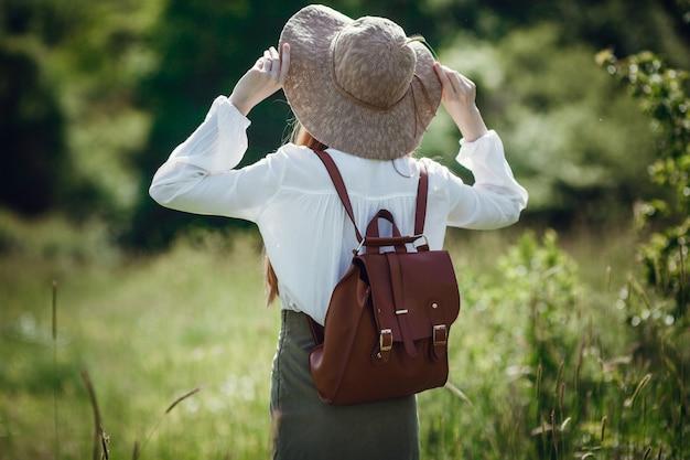 Schöne junge frau mit roten haaren, in einem hut und mit einem rucksack am rande des waldes.