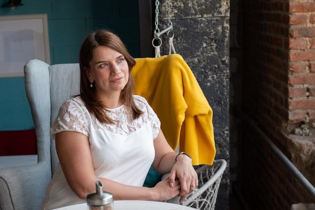 Schöne junge frau mit roten langen haaren in einer weißen bluse, die allein auf einem stuhl in einem café sitzt und auf ihre bestellung wartet.