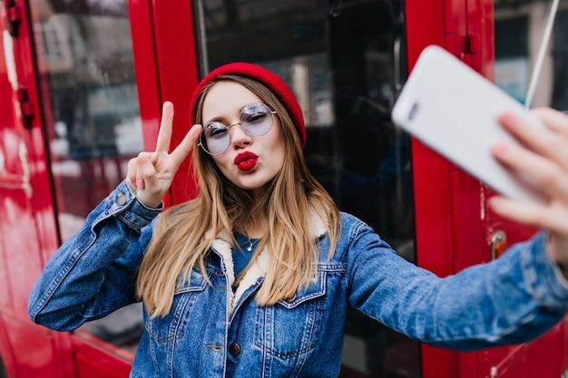 Schöne junge frau mit roten lippen, die selfie im frühlingstag machen und telefon benutzen.