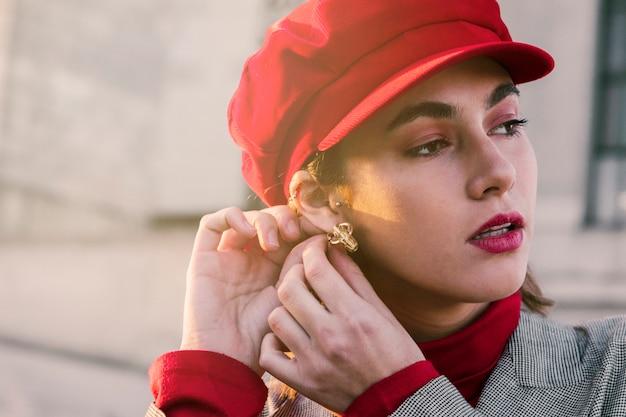 Schöne junge frau mit roter kappe über ihren tragenden ohrringen des kopfes im ohr