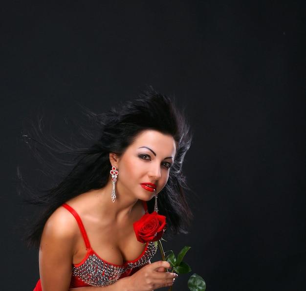 Schöne junge frau mit roter rose auf dunklem hintergrund