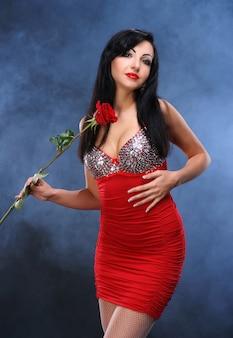 Schöne junge frau mit roter rose auf rauchigem hintergrund