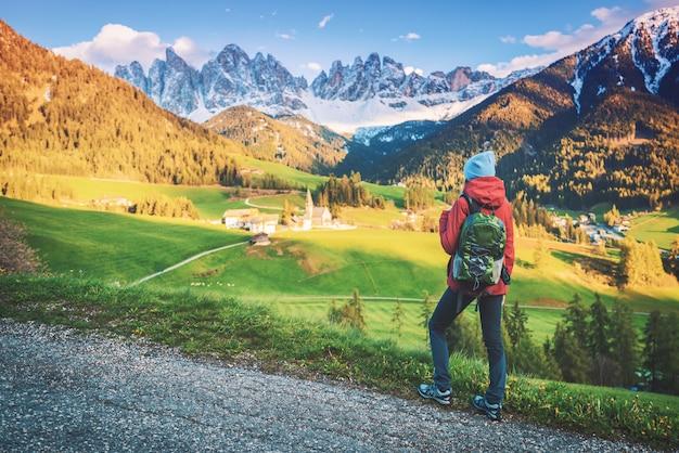 Schöne junge frau mit rucksack steht auf dem hügel in den bergen bei sonnenuntergang im herbst.