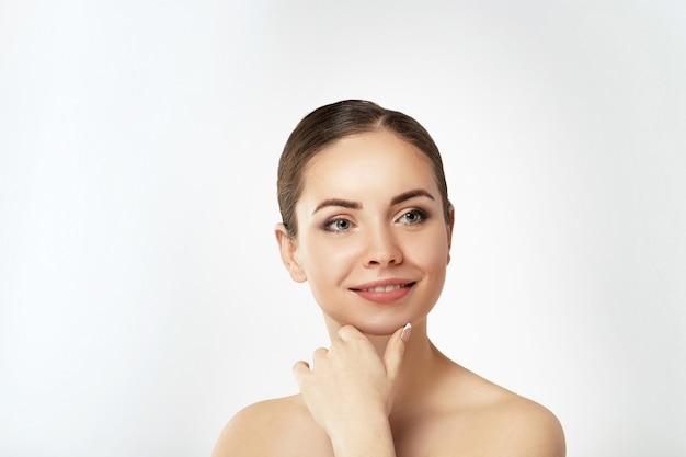 Schöne junge frau mit sauberer frischer haut berühren eigenes gesicht. gesichtsbehandlung. kosmetologie, schönheit und spa. hautpflege. modell mit natürlichem make-up