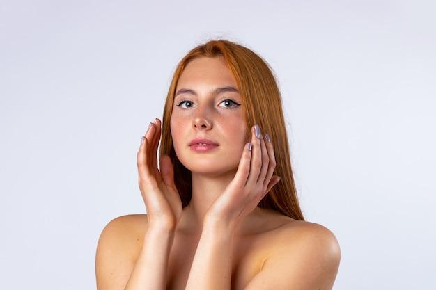 Schöne junge frau mit sauberer frischer haut, die ihr eigenes gesicht berührt. gesichtsbehandlung. kosmetologie, schönheit und spa. foto auf weißer wand. hochwertiges foto