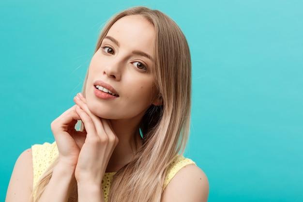 Schöne junge frau mit sauberer perfekter haut. porträt des schönheitsmodells, das ihr gesicht berührt. spa, hautpflege und wellness. nahaufnahme, blauer hintergrund, exemplar.