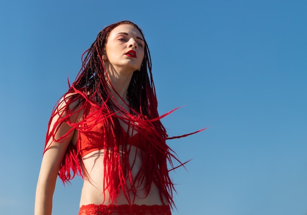 Schöne junge frau mit scharlachroten dreadlocks und rotem badeanzug, die die natur genießt.