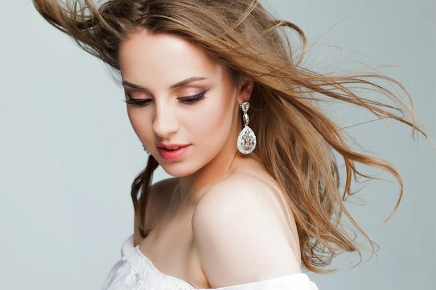 Schöne junge frau mit schönen ohrringen, porträt nahaufnahme. fliegende haare