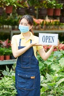 Schöne junge frau mit schutzmaske, wenn sie kunden im gartencenter einlädt