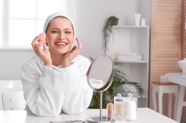 Schöne junge frau mit schwamm, der make-up zu hause anwendet