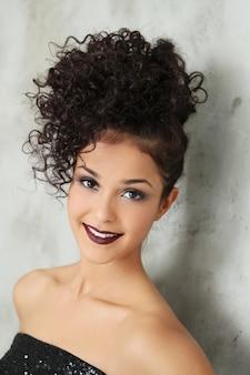 Schöne junge frau mit schwarzen lockigen haaren und schwarz glänzendem kleid