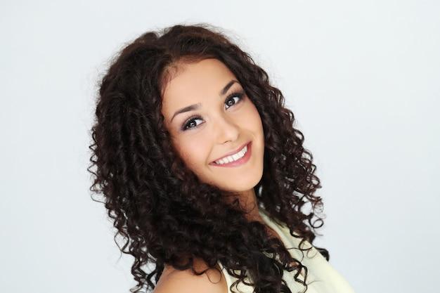 Schöne junge frau mit schwarzen lockigen haaren