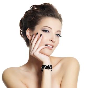 Schöne junge frau mit schwarzer maniküre und stilvoller frisur, die auf weiß aufwirft