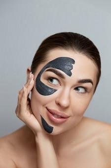 Schöne junge frau mit schwarzer maske des tons auf gesicht reinigen frische haut. mädchen schönheit gesichtspflege. gesichtsbehandlung . reinigungsmaske