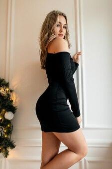 Schöne junge frau mit sexy beinen im eleganten schwarzen kleid steht in der nähe einer weißen wand im zimmer