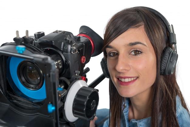 Schöne junge frau mit slr-videokamera und kopfhörern