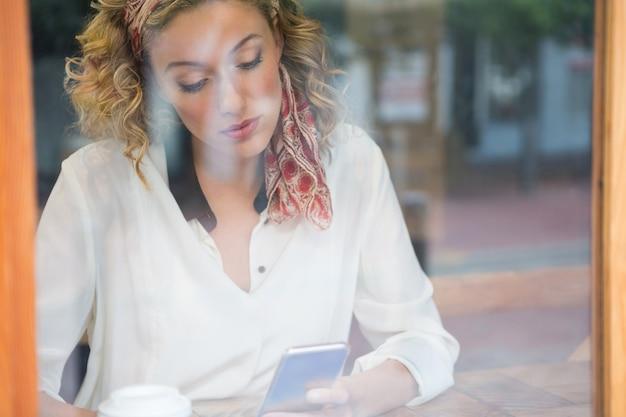 Schöne junge frau mit smartphone im café durch fenster gesehen