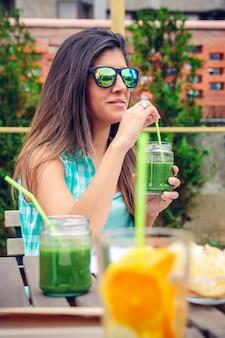 Schöne junge frau mit sonnenbrille, die draußen grünen gemüsesmoothie mit stroh trinkt. gesundes bio-getränkekonzept.