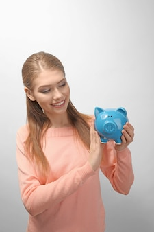 Schöne junge frau mit sparschwein auf heller oberfläche