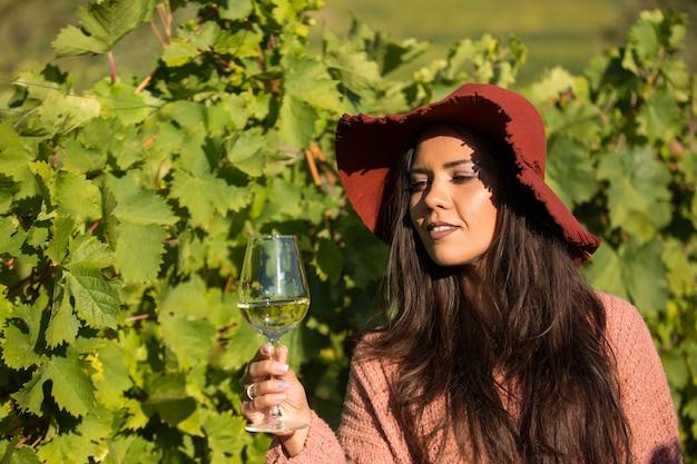 Schöne junge frau mit stilvollem hut in einem weinberg, der ein glas weißwein hält. porträt des schönen brunette im weinberg.