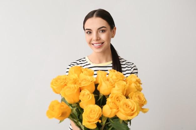 Schöne junge frau mit strauß rosen auf grauer oberfläche