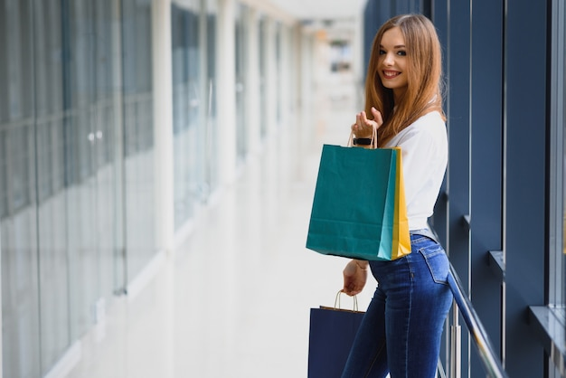 Schöne junge frau mit taschen im einkaufszentrum